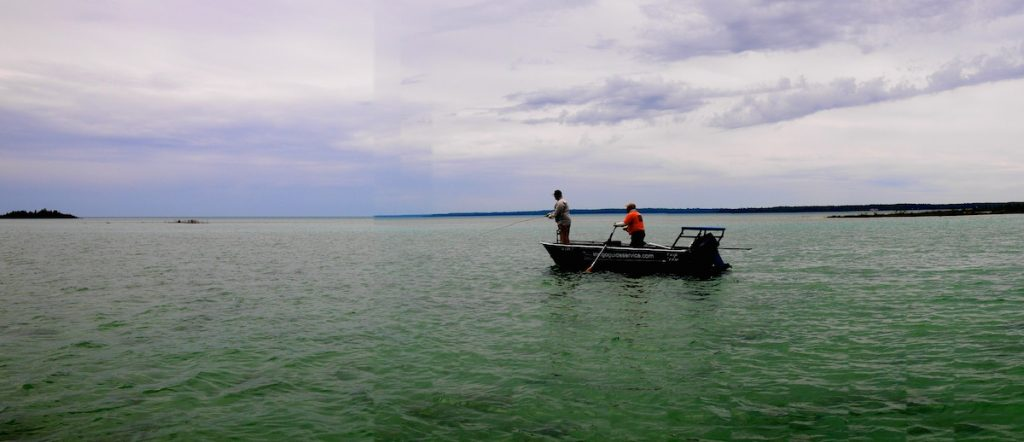 Guide Steve Martinez pushes Cameron Mortenson across a Great Lakes flat.